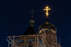 A glowing Orthodox cross is located on the golden dome of the Orthodox Christian church, restoration works are being carried out. Scaffolding, night view Stock Photos