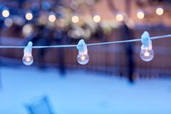 Glowing party lights outdoors in winter. With snow on the ground and copy space for your festive or Christmas greeting royalty free stock photos