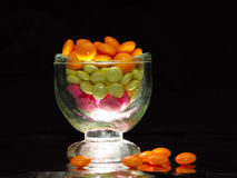 Glowing pills in glass. Glowing glass full of pills on dark background Royalty Free Stock Image