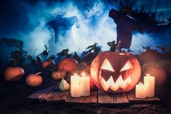 Glowing pumpkin with blue mist and scarecrows for Halloween. On dark background Royalty Free Stock Image