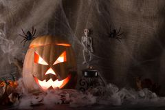 Glowing pumpkin Halloween background spider webs, smoke and spiders Royalty Free Stock Image