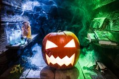 Glowing pumpkin for Halloween in witcher hut with color smoke Royalty Free Stock Photography
