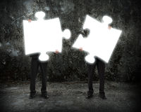 Glowing puzzles businessmen hold to connect illuminating dark co Royalty Free Stock Images