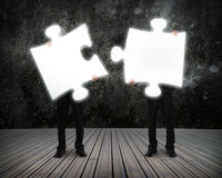 Glowing puzzles businessmen hold to connect illuminating dark wo Stock Photos