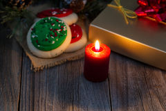 Glowing red candle with gift box and cookies on rustic wood Stock Images