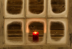 Glowing red candle in snow covered window Royalty Free Stock Images