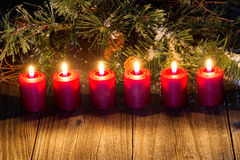 Glowing red candles with snow covered evergreen branch on rustic Royalty Free Stock Images