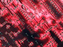 Glowing red circuits. Back lit red circuit board macro Stock Photo