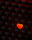 Glowing red-glass heart surrounded by dark hearts Royalty Free Stock Images