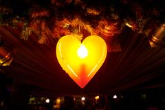 Glowing red heart-shaped lamp on a black background royalty free stock image