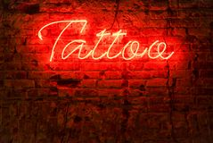 Glowing red neon signboard word tattoo stock images