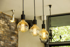 Glowing retro light bulbs hanging from ceiling. In room Royalty Free Stock Image