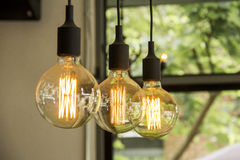 Glowing retro light bulbs hanging from ceiling. In room Stock Photos