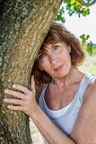 Glowing 50s woman smiling,touching a tree. Middle aged wellness - glowing 50s woman smiling,touching a tree for metaphor of mature wellness,summer daylight royalty free stock image