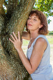 Glowing 50s woman touching a tree in harmony with nature. Middle aged wellness - glowing 50s woman touching a tree in harmony with nature for respect of Stock Photos