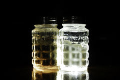 Glowing Salt and Pepper Shakers. Glass, backlit salt and peppershaker royalty free stock images