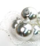Glowing Silver Ornaments. Cut glass bowl containing glowing silver Christmas ornaments. Short depth of field, white background Stock Image