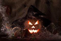 Glowing a sinister pumpkin lantern with black witch hat on dark Stock Images