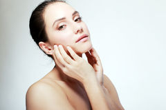 Glowing skin. Front portrait of the woman with beauty face and hands and glowing skin -  on white Royalty Free Stock Images