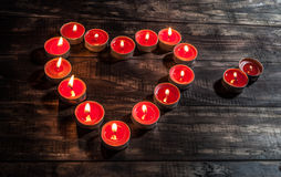 Glowing small red candles arranged in heart shape Stock Photography