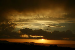 Glowing South African sunset. Sun setting or rising behind dark rain clouds after or before rain Stock Photo