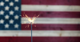 Glowing sparkler with rustic wooden flag of United States of Ame Royalty Free Stock Photos