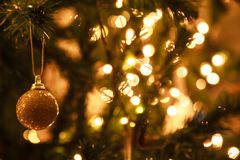 Glowing Sparkling Gold defocused Light Illumination background with decorated Christmas Tree. Happy Holidays, Festival design Royalty Free Stock Photos