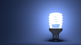 Glowing spiral light bulb on blue Royalty Free Stock Image