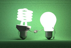 Glowing spiral light bulb character and tungsten one handshaking Royalty Free Stock Photography