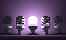 Glowing spiral Light bulb among dead ones on violet Royalty Free Stock Image