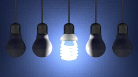 Glowing spiral light bulb among dead tungsten ones hanging on blue Royalty Free Stock Photos