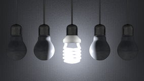 Glowing spiral light bulb among dead tungsten ones hanging on gray Royalty Free Stock Photo