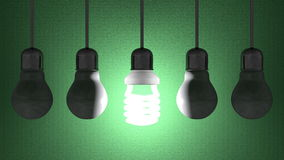Glowing spiral light bulb among dead tungsten ones hanging on green Stock Photos