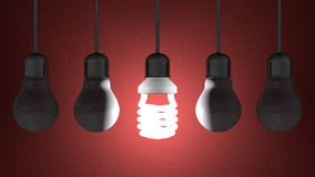 Glowing spiral light bulb among dead tungsten ones hanging on red Stock Photo