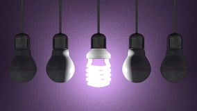 Glowing spiral light bulb among dead tungsten ones hanging on violet Royalty Free Stock Images
