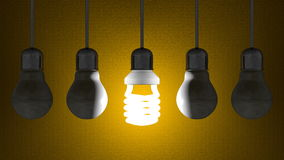 Glowing spiral light bulb among dead tungsten ones hanging on yellow Stock Images