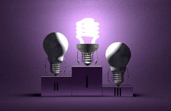 Glowing spiral light bulb and dead tungsten ones on podium Royalty Free Stock Photos