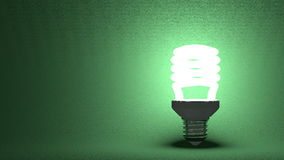 Glowing spiral light bulb on green Royalty Free Stock Photo