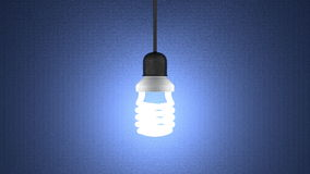 Glowing spiral light bulb hanging on blue Royalty Free Stock Photo