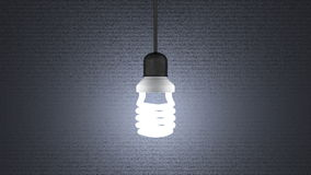Glowing spiral light bulb hanging on gray Royalty Free Stock Photo