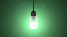 Glowing spiral light bulb hanging on green Stock Photo