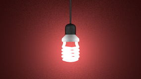 Glowing spiral light bulb hanging on red Stock Photos
