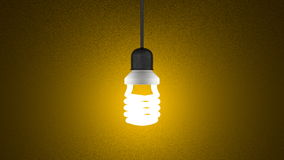 Glowing spiral light bulb hanging on yellow Stock Images