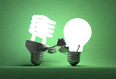 Glowing spiral light bulb punching tungsten one with its fists Royalty Free Stock Photos