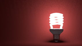 Glowing spiral light bulb on red Royalty Free Stock Photo