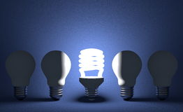Glowing spiral light bulb in row of dead tungsten ones on blue Royalty Free Stock Photos