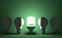 Glowing spiral light bulb in row of dead tungsten ones on green Stock Photo