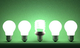 Glowing spiral light bulb in row of tungsten ones on green Royalty Free Stock Photos
