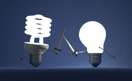 Glowing spiral light bulb and tungsten one fighting duel Royalty Free Stock Photos