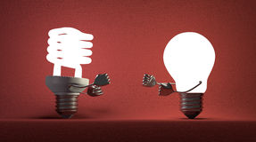 Glowing spiral light bulb and tungsten one fighting with fists. Glowing fluorescent light bulb and tungsten one fighting with their fists on red textured Royalty Free Stock Images